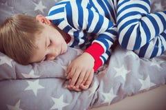 Netter kleiner Junge schläft in den pajames auf Bett Fokus oben Lizenzfreies Stockfoto