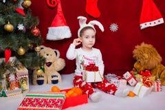 Netter kleiner Junge sitzt mit einem Weihnachtsgeschenk Stockfotografie