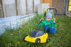 Netter kleiner Junge sitzt nahe einem Rasenmäher lizenzfreie stockfotografie