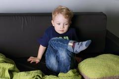 Netter kleiner Junge sitzt und denkt auf schwarzer Couch Stockfotos