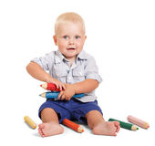 Netter kleiner Junge sitzt und große Bleistifte halten lokalisiert Lizenzfreies Stockfoto