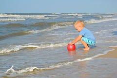 Netter kleiner Junge spielt mit Ball auf der Küste stockfotos