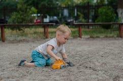 Netter kleiner Junge spielt mit einem Spielzeug auf dem Spielplatz Stockfotografie