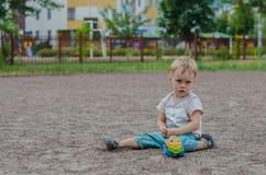 Netter kleiner Junge spielt mit einem Spielzeug auf dem Spielplatz Lizenzfreie Stockfotografie