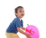 Netter kleiner Junge spielt mit rosafarbenem Ballon Lizenzfreies Stockbild