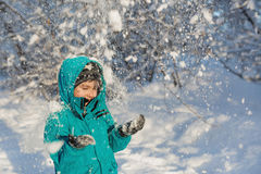 Netter kleiner Junge steht unter fallendem Schnee Stockfotografie