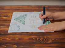 Netter kleiner Junge am Tisch mit seiner Zeichnung und Bleistift Lizenzfreies Stockbild