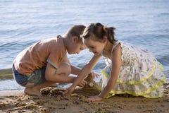 Netter kleiner Junge und Mädchen, die im Sand spielt lizenzfreies stockbild