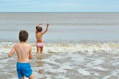 Netter kleiner Junge und Mädchen, spielend in der Welle auf Strand Lizenzfreie Stockfotografie