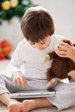 Netter kleiner Junge und sein Affe spielen und spielen auf Tablette Lizenzfreie Stockbilder