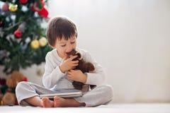 Netter kleiner Junge und sein Affe spielen und spielen auf Tablette Stockfotos