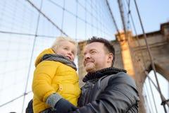 Netter kleiner Junge und sein Vater auf Brooklyn-Brücke mit Wolkenkratzern auf Hintergrund lizenzfreies stockfoto