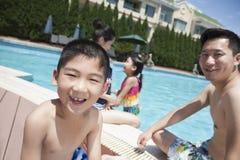 Netter kleiner Junge und seine Familie, die im Pool spielt stockfotos