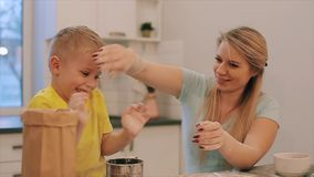 Netter kleiner Junge und seine schöne Mutter in den bunten Hemden sind spielend und beim Kneten des Teigs in lachend stock footage