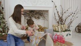 Netter kleiner Junge, welche seiner Mutter hilft, Papier für Weihnachtsgeschenke oben einwickeln zu schneiden stock video footage