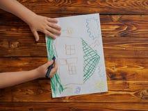Netter kleiner Junge zeichnet Bleistift ein Haus Stockfoto