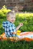 Netter kleiner Junge zeichnet in Sommerpark lizenzfreie stockbilder