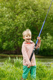 Netter kleiner Jungenstand nahe einem Fluss mit einer Angelrute in seinen Händen Lizenzfreie Stockbilder