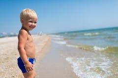 Netter kleiner kaukasischer Junge mit dem Lächeln, das auf dem Seestrand steht Stockfotos