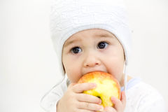Netter kleiner kaukasischer Junge 11 Monate alte sitzt und isst roten Apfel auf weißem Hintergrund Stockbild