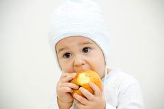 Netter kleiner kaukasischer Junge 11 Monate alte sitzt und isst roten Apfel auf weißem Hintergrund Stockbilder