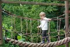 Netter kleiner Kleinkindjunge, der Spaß mit dem Klettern auf Spielplatz I hat Stockbild