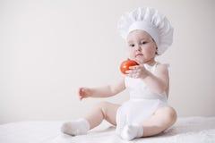 Netter kleiner Koch isst Tomate Stockfoto