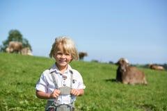 Netter kleiner lächelnder bayerischer Junge auf einem Landfeld während Oktoberfest in Deutschland Stockbild