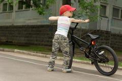 Netter kleiner Machojunge mit seinem Fahrrad Lizenzfreie Stockfotografie