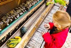 Netter kleiner Musiker, der altes gebrochenes Klavier im Park spielt Stockfotos