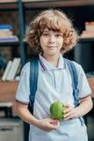 netter kleiner Schüler mit Apfel lizenzfreies stockbild