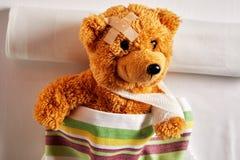 Netter kleiner Teddybär mit einem Arm in einem Riemen stockfotografie