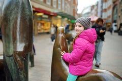 Netter kleiner Tourist, der auf populärer Skulptur der Schweinfamilie, des Schweinehirts und seines Hundes in Bremen sitzt Lizenzfreie Stockfotografie