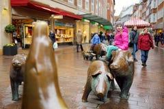 Netter kleiner Tourist, der auf populärer Skulptur der Schweinfamilie, des Schweinehirts und seines Hundes in Bremen sitzt Lizenzfreies Stockfoto