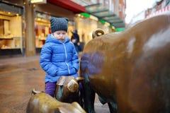 Netter kleiner Tourist, der auf populärer Skulptur der Schweinfamilie, des Schweinehirts und seines Hundes in Bremen sitzt Stockfotografie