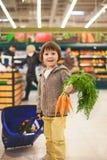 Netter kleiner und stolzer Junge, der beim Einkauf, gesund hilft Stockbilder