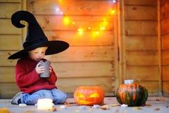 Netter kleiner Zauberer, der auf Kerze schaut lizenzfreies stockbild