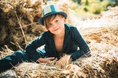 Netter kleines Kinderjunge, der Goldblatt auf Bauernhofdorfhintergrund hält Kinderjunge liegt auf dem Heu Junge im Hut sind lizenzfreies stockbild