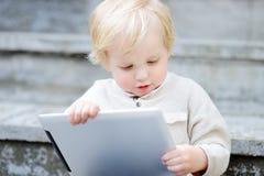 Netter Kleinkindjunge, der mit einer digitalen Tablette spielt Stockfotografie