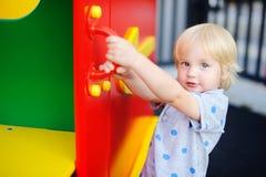 Netter Kleinkindjunge, der Spaß auf Spielplatz hat Stockfoto