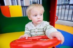 Netter Kleinkindjunge, der Spaß auf Spielplatz hat Lizenzfreie Stockbilder