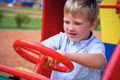 Netter Kleinkindjunge, der Spaß auf Spielplatz hat Des Active Spiel draußen für kleine Kinder Stockfotografie