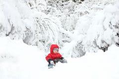 Netter Kleinkindjunge in der Winterklage, die auf einer großen Schneewehe, surr sitzt Stockfotografie