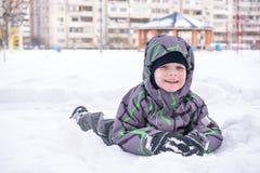 Netter Kleinkindjunge im bunten Winter kleidet die Herstellung des Schneeengels Stockbild