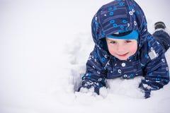 Netter Kleinkindjunge im bunten Winter kleidet die Herstellung des Schneeengels Stockbilder
