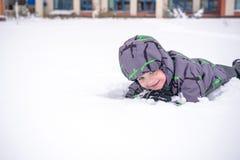 Netter Kleinkindjunge im bunten Winter kleidet an niederlegen Lizenzfreie Stockfotografie
