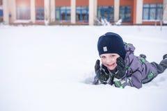 Netter Kleinkindjunge im bunten Winter kleidet an niederlegen Des Active Freizeit draußen mit Kindern herein Glückliches Kind Stockfotografie