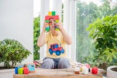 Netter Kleinkindjunge mit dem Spielen mit vielen buntem Plastik blockiert Innen Aktives Kind, das Spaß mit Gebäude hat und Stockbild