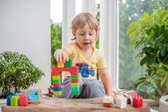 Netter Kleinkindjunge mit dem Spielen mit vielen buntem Plastik blockiert Innen Aktives Kind, das Spaß mit Gebäude hat und Lizenzfreie Stockbilder