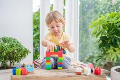 Netter Kleinkindjunge mit dem Spielen mit vielen buntem Plastik blockiert Innen Aktives Kind, das Spaß mit Gebäude hat und Stockfotografie